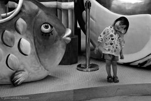 Little smiling Chinese girl near the statue of a giant fish.