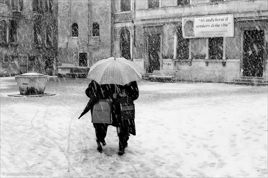 Two women are walking under an umbrella against the snow on Campo San Silvestro, Venice, Italy