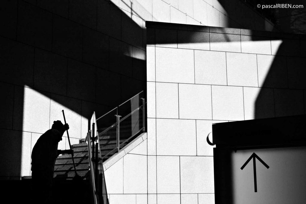 Ginza, Early Morning - The silhouette of a woman is cleaning a stair trapped inside strong shadows.