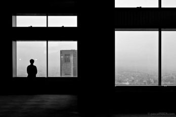 A man contemplates Tokyo across the bay window from the high floor of a building.