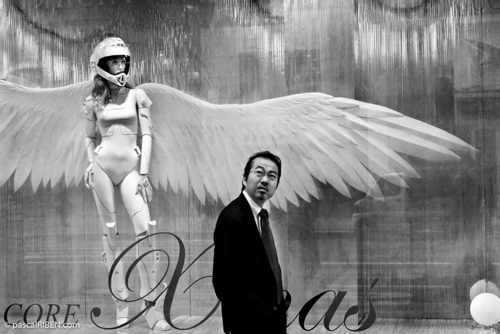 A Japanese man walk in front of a shop showcasing a woman angel in Ginza District, Tokyo, Japan