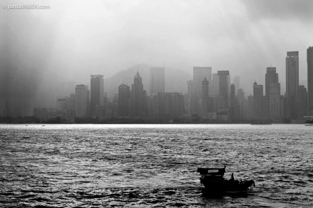 Small boat in Hong Kong harbor with Victoria Skyline in the background, seen from Avenue of Stars, on an early morning