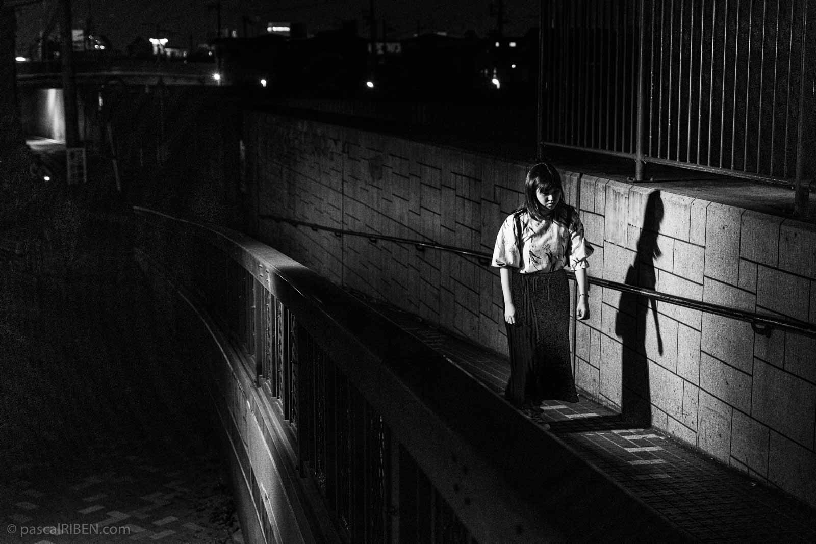 In Daitō, a young woman climbs the access ramp allowing pedestrians and cyclists to cross the bridge spanning the Onji River.