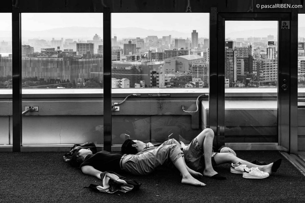 A couple is taking a nap at Kaze-no-hiroba plaza, located on the 11th floor of Osaka Station City.