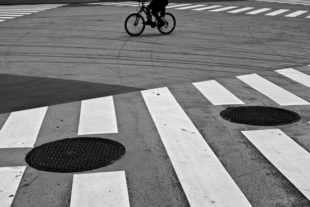 Bicycle wheels and manhole covers with crosswalk in Tokyo, Japan.