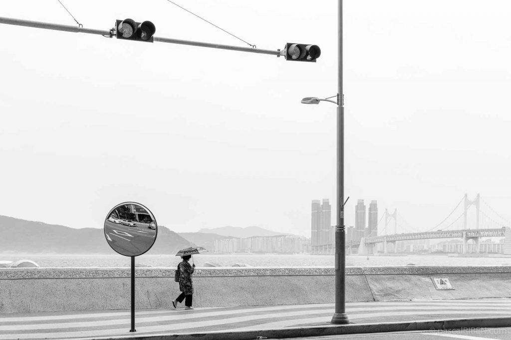 A woman with an umbrella against the sun walks along Marine City in Busan, with Gwangandaegyo Bridge in the background.