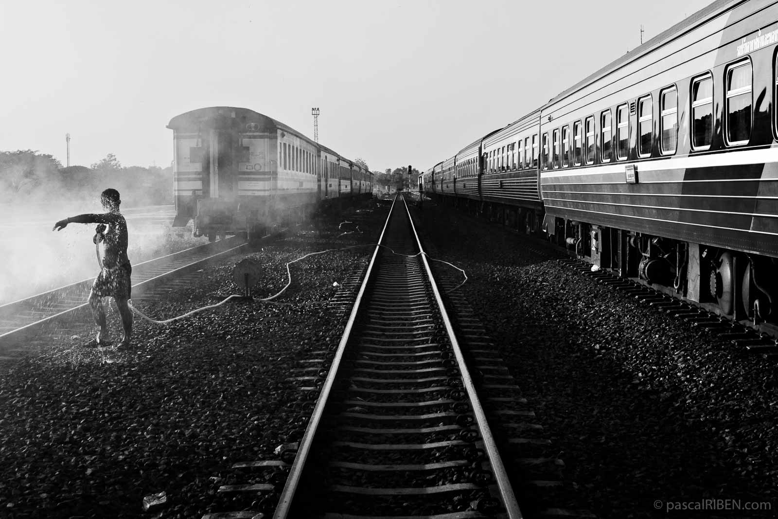 A man is taking a shower on the tracks at Nong Khai railway station in Thailand.